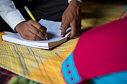 Rahidul Islam making notes during his interview with a garment worker called Kohinur in her home in Dhaka, Bangladesh. <br /> <br /> Rahidul works for the BRAC microfinance, financial diaries project. This programme works to improve the financial literacy of garment workers.