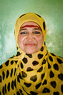 Oman, Al-Hamra. Portrait of an Omani woman wearing yellow dress and perfumes on her forehead.