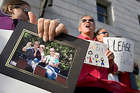 SAN FRANCISCO - SEPTEMBER 8:  (L-R) Michelle Kletter holds a photograph of her family as she and Monika Sharp and Angela Sharp-Sabatino joins a group of supporters for the Same Sex Marriage Bill gather in front of California Supreme Court building on September 8, 2005 in San Francisco, California. With the same sex bill passing in the State Legislature the fate of many California same sex couples is now up to California Governor Arnold Schwarzenegger who is expected to veto the bill. (Photo by David Paul Morris)