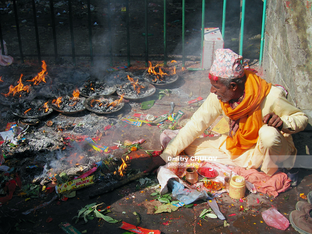 Pharping, Nepal - November 26, 2005: Unidentified Nepali man wearing traditional dress burns candles in Dakshinkali Hindu temple in Pharping, Nepal.