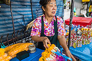 12 APRIL 2014 - BANGKOK, THAILAND: A woman sells flower garlands for the Phra Buddha Sihing statue during the stop for the Phra Buddha Sihing procession in Thonburi. The Phra Buddha Sihing, a revered statue of the Buddha, is carried by truck through the streets of Bangkok so people can make offerings and bathe it in scented oils. Songkran is celebrated in Thailand as the traditional New Year's from 13 to 16 April. The date of the festival was originally set by astrological calculation, but it is now fixed. The traditional Thai New Year has been a national holiday since 1940, when Thailand moved the first day of the year to January 1. The first day of the holiday period is generally the most devout and many people go to temples to make merit and offer prayers for the new year.    PHOTO BY JACK KURTZ