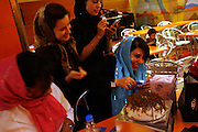 A group of fashionable teenagers celebrate a friend's birthday with presents in Dora the Explorer wrapping paper and cake at a restaurant in Shiraz.  One checks her PDA as the others  playfully put icing on the birthday girl's  face.