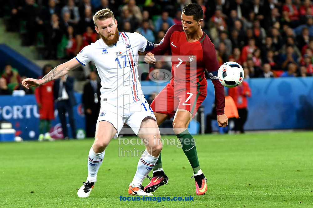 Aron Gunnarsson of Iceland (left) and Cristiano Ronaldo of Portugal (right) during the UEFA Euro 2016 match at Stade Geoffroy-Guichard, Saint-&Eacute;tienne, France<br /> Picture by Kristian Kane/Focus Images Ltd 07814482222<br /> 14/06/2016