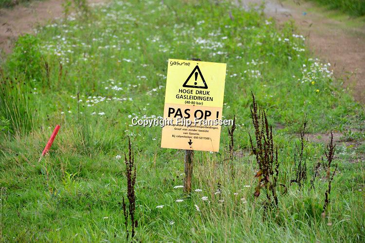 Nederland, Beunigen, 9-8-2016Een paaltje met bord, waarschuwingsbord, van de Gasunie in een gebied waar gegraven wordt om een stadsvijver aan te leggen, om aan te geven waar een gasleiding in de grond ligt. graven, graafwerkzaamheden,bouw,waarschuwing,bodem,trace,grond,Foto: Flip Franssen