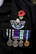 Metropolitan Policeman wearing poppy and army medals on Remembrance Sunday
