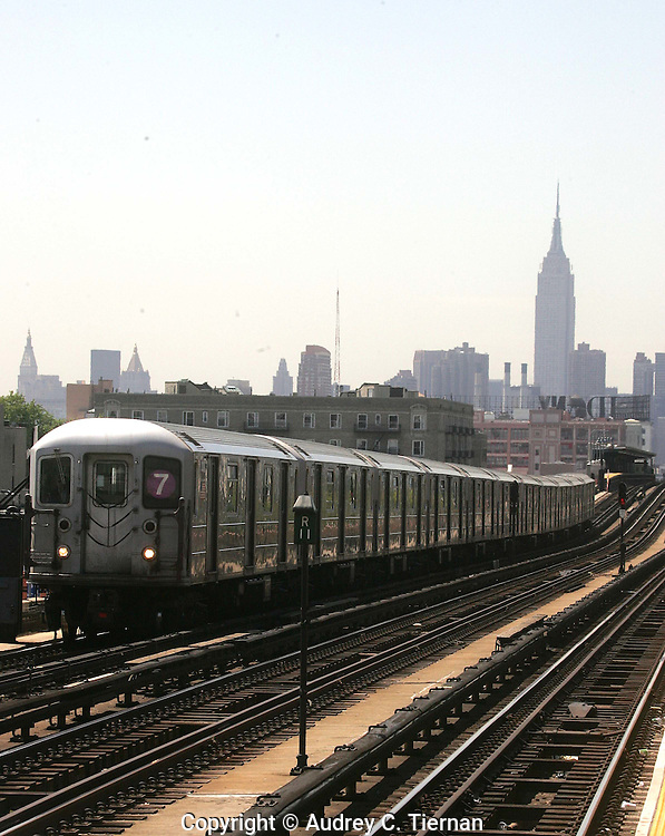 Long Island City, NY:  Friday, May 14, 2005-- The 7 subway train along it's route in Queens with the Empire State Building in the background.   ©Audrey C. Tiernan