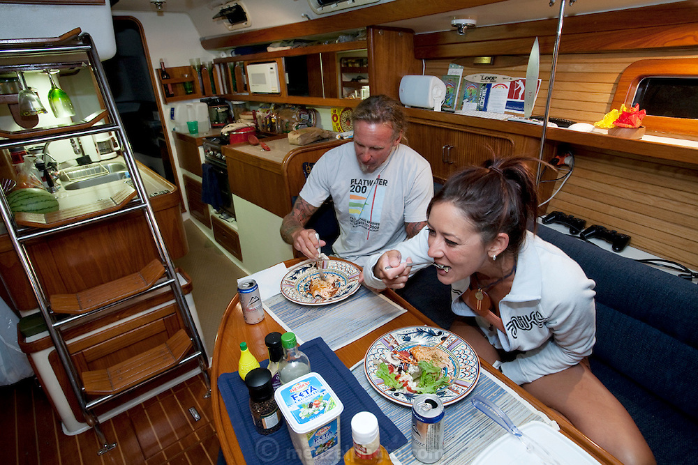 Ernie Johnson, a finish carpenter and paddle surfer, dining on grilled salmon with his wife Andie on their 38 foot sailboat where they live docked at Dana Point Harbor, California..   (From the book What I Eat: Around the World in 80 Diets.) The caloric value of his day's worth of food in the month of September was 3500 kcals. He is 45 years of age; 5 feet, 10 inches tall; and 165 pounds.