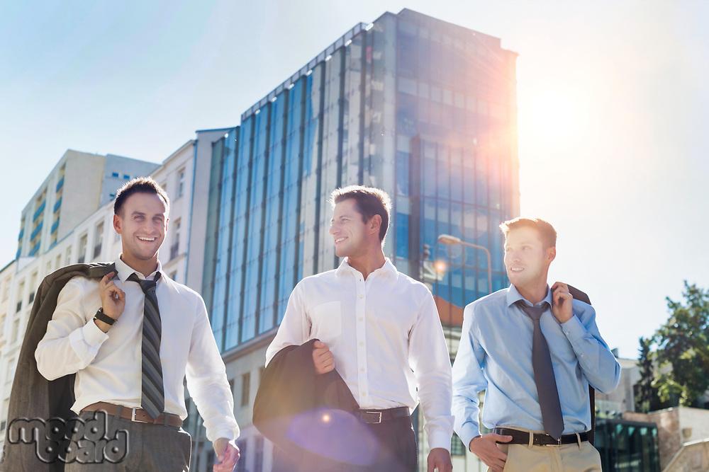 Portrait of handsome mature businessmen walking while talking after work
