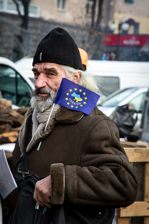 "An old man, wearing a small European flag on his coat, with the inscription ""Ukraine"" inside the circle of stars."