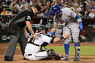 Aug 11, 2017; Phoenix, AZ, USA; Chicago Cubs infielder Javier Baez (9) and umpire Mike Muchlinski (76) help up Arizona Diamondbacks catcher Chris Herrmann (10) after being hit by Baez's bat on a follow through swing in the sixth inning at Chase Field. Mandatory Credit: Jennifer Stewart-USA TODAY Sports