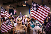 04 JULY 2012 - PHOENIX, AZ:  MARGARITA BASRTO, originally from Mexico, and SUMAYO AHMED, originally from Somalia, wave American flags after being naturalized as US citizens Wednesay. About 250 people, from 62 countries, were naturalized as US citizens during the 24th Annual Fiesta of Independence naturization ceremony at South Mountain Community College in Phoenix Wednesday. The ceremony was presided over by the Honorable Roslyn O. Silver, Chief United States District Court Judge.   PHOTO BY JACK KURTZ