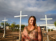 Cindy Tuzon erected crosses in her yard near the I-10 corridor in Tucson, Arizona.  The three crosses represent those of the crucifixion of Christ, a belief in Christianity.  Many passersby, especially truckers on Interstate 10, acknowledge her message by honking their horn.  Tuzon said that a woman whose car broke down on the freeway said she came to her home for assistance because she felt safe when she saw the crosses.  Tuzon shares her home with her husband, Robert, and their daughter.
