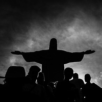 This is one of the most photographed icons on the planet. The statue of the Christ in Rio, Brazil. <br /> <br /> After searching for something original, I got it! What I love about this image are two things. 1 - its silhouette, and 2 - the statue seems to be a part of the people, within the crowd.