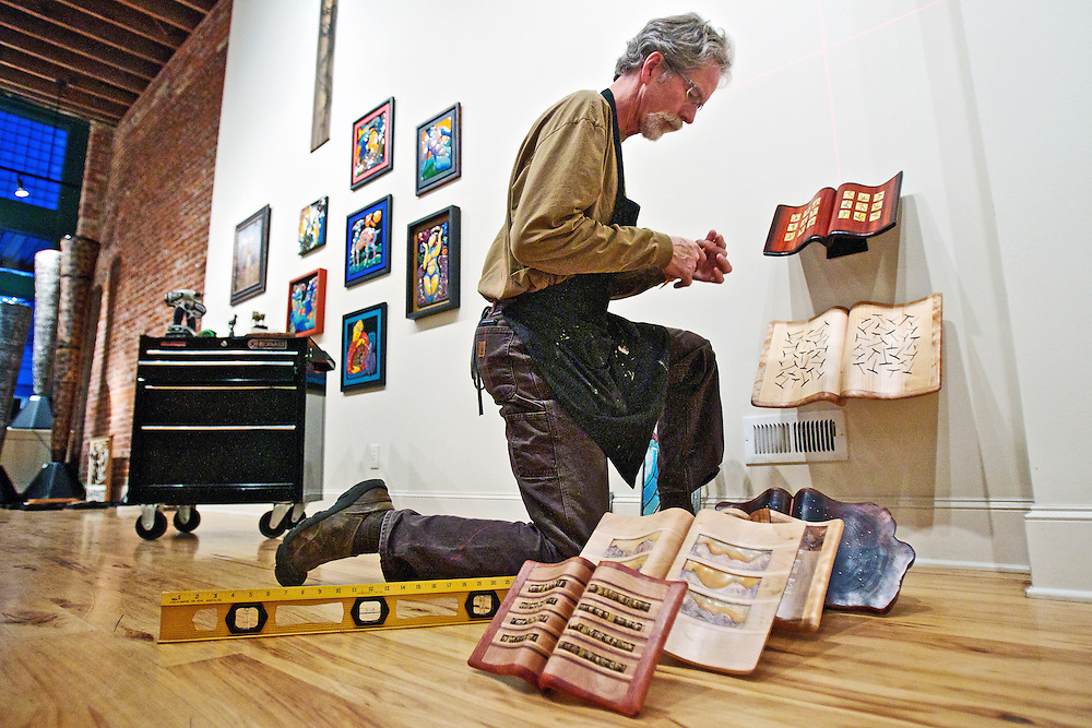 Steve Gibbs hangs Morse Clary's wooden book art pieces Tuesday at The Art Spirit Gallery of Fine Art in preparation for the 13th annual Small Artworks Invitational at the downtown Coeur d'Alene gallery Friday.