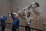 Visitors pose in front of the British Museum's Elgin Marbles that originate from the Parthenon in Athens, on 28th February 2017, in London, England.