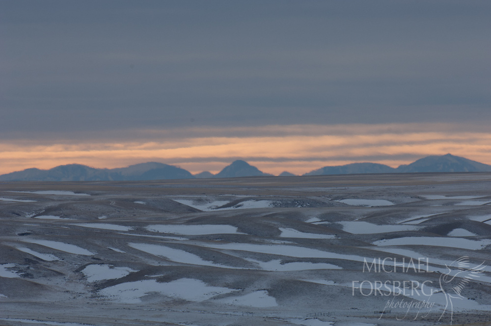 Phillips County, Glaciated Plains, Montana<br /> <br /> Milk River breaks, snowfields and Little Rockies (?) landscape at sunset