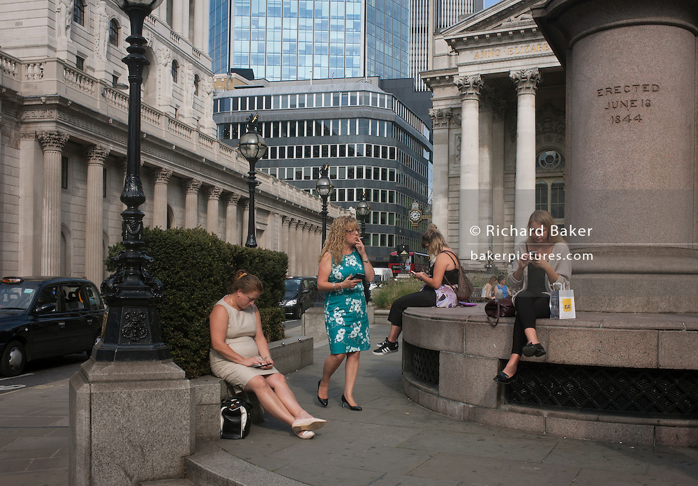 Lunchtime City workers enjoy sunshine near the Bank of England during an unusual autumn heatwave on 13th September 2016, in the City of London, England.