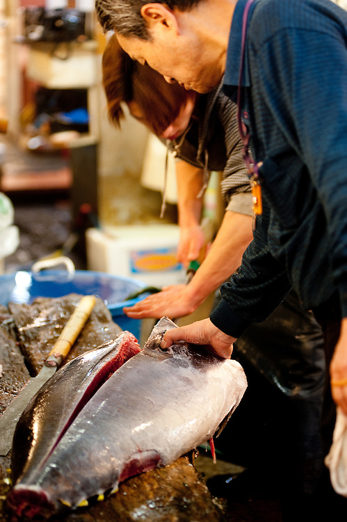 Workers use a maguro bocho (tuna knife) to cut up a yellowfin tuna.