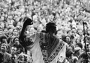 Co creators singer dressed in african style robe, dances while large audience watch. Glastonbury 1993