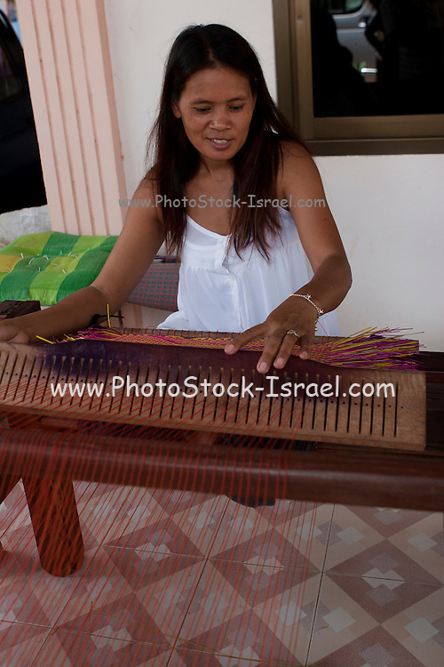 Thailand. Woman weaving on a hand loom