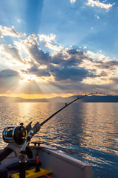 """Fishing Pole at Lake Tahoe 10"" - Photograph of a fishing pole at Lake Tahoe with crepuscular rays in the sky. Shot near sunrise during the annual Jakes on the Lake charity fishing derby."