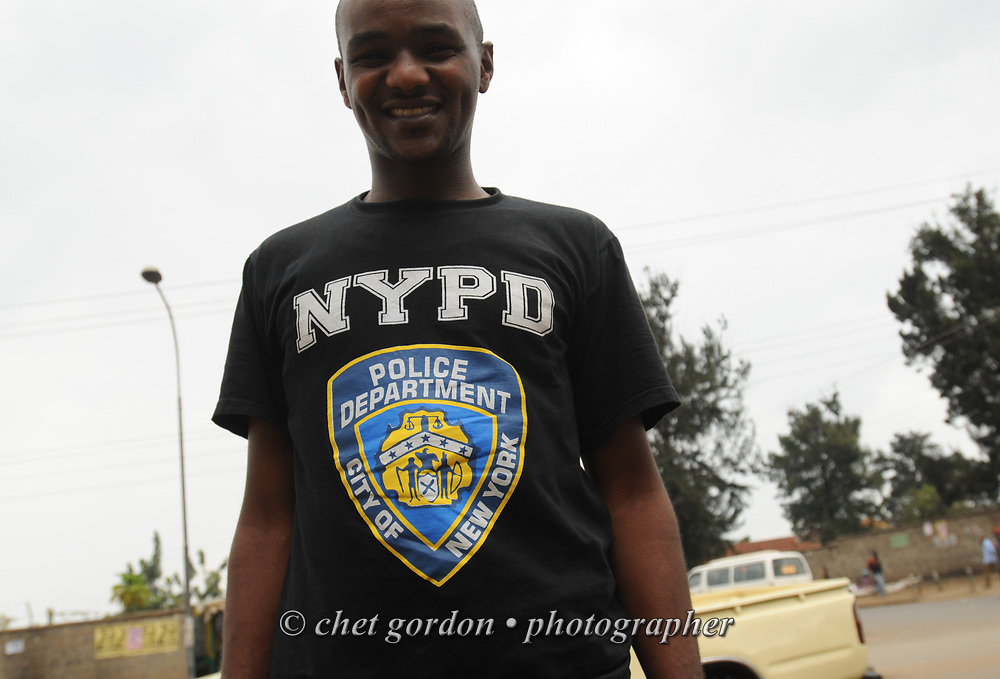 NAIROBI, KENYA.  A Kenyan man wears a NY Police Dept. t-shirt at a matatu / bus stop along Outer Ring Road in Nairobi, Kenya on Thursday, December 1, 2011.  © Chet Gordon/THE IMAGE WORKS