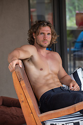 shirtless muscular man at home on a patio bench