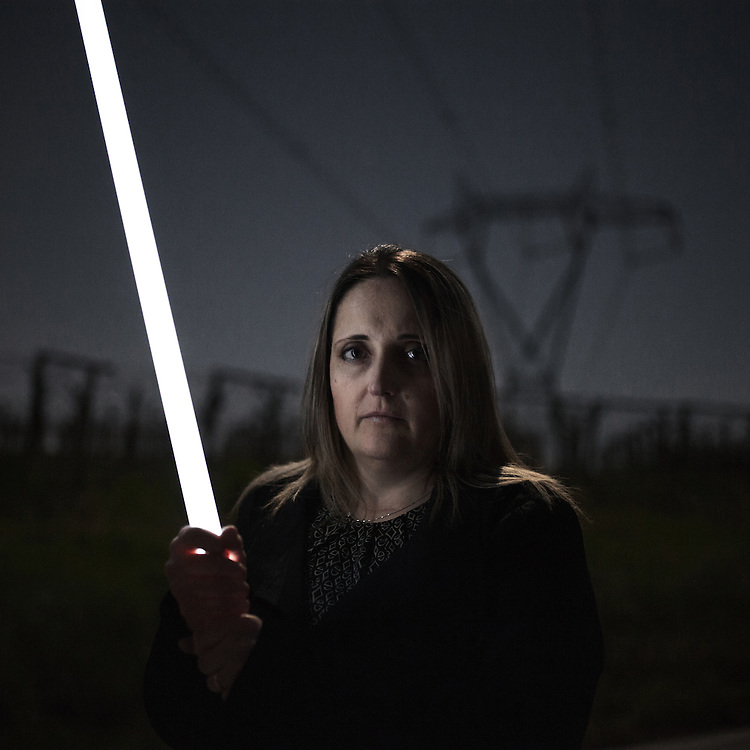 Mirella Di Rosa holds a neon tube that, because of the Tesla effect, ignites spontaneously under the wires of a power line in the Frentano valley. irella refused a &quot;friendly&quot; agreement from the construction company for the passage of the power line, for just 4.000 Euros for a land that that is worth at least 200.000 Euros. The company carrying out the work has enetered the property without any authorization to perform surveys and geological investigations.<br /> &quot;I had a dream: to start a new life with a new family. A new home on the land inherited form my parents. A project in which I had put all my expectations, which were destroyed when I learned fro the city hall that I was no longer allowed to lay one single brick on my land&quot;.<br /> Sant'Onofrio (CH)