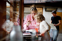 Foreign Cinema chef and owner Gayle Pirie takes a break to help feed her daughter, Pearl, 3, dinner of macaroni and cheese during a lull in dinner, as her husband, John Clark, right, reviews the wine menu, in San Francisco, CA., on Friday, June 12, 2009.