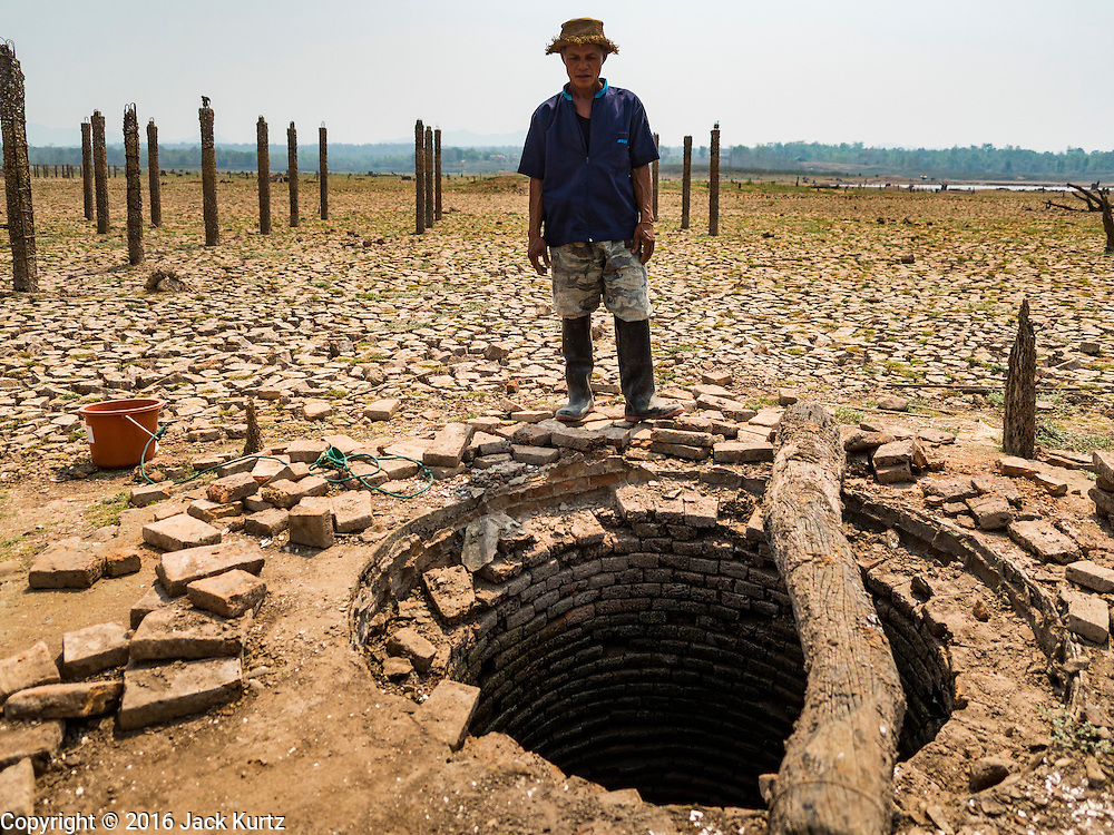 31 MARCH 2016 - NA SAK, LAMPANG, THAILAND: A farmer looks at the old community well, which still has water in it, in the Mae Chang Reservoir. This is first time the well has been accessible in more than 30 years, although no one lives in the area to use the water from the well. The Mae Chang Reservoir in Lampang province was created more than 30 years ago when the Chang River was dammed. Five villages along the river were relocated to hillsides above the river. For the first time since it was flooded, the reservoir is nearly empty and the ruins of the old villages are visible. Many people who remember the old villages are coming down to the ruins to visit them. This part of Thailand hasn't received significant rain in months and many irrigation canals and streams are running dry.    PHOTO BY JACK KURTZ
