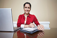 Business woman writing in diary beside laptop in office, portrait