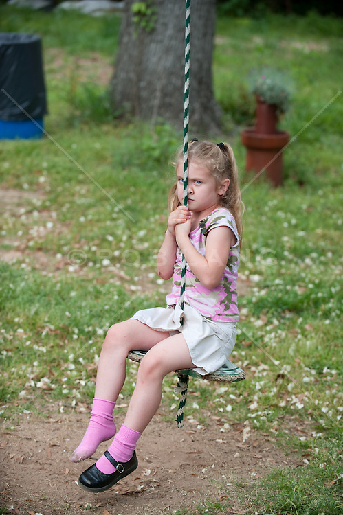 Young girl with one shoe seated on a rope swing