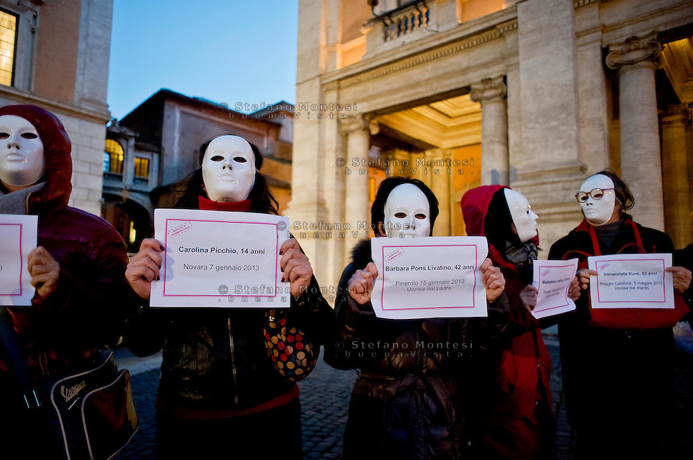 Roma  25 Novembre 2013<br /> Manifestazone in Campidoglio nella  Giornata internazionale contro la violenza sulle donne a Roma. Manifestanti con un cartello con i nomi delle donne uccise<br /> Rome, Italy. 25th November 2013 -- The capitol in Rome glows red with a call to end violence against women is projected on the building. -- The capitol in Rome is lit red in observance of the International Day to stop violence against women. Protesters sign with the names of women killed