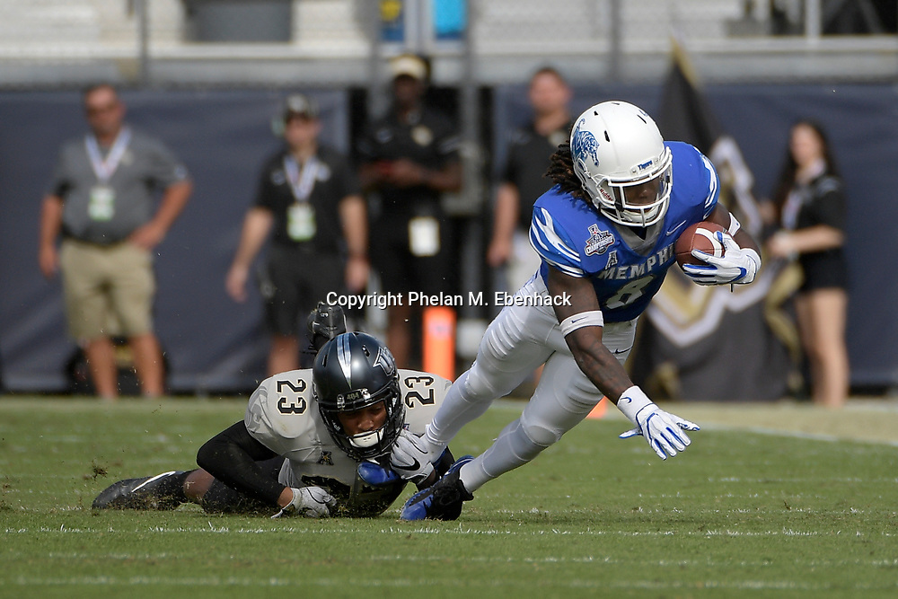 Memphis running back Darrell Henderson (8) is tackled by Central Florida defensive back Tre Neal (23) after rushing for yardage during the first half of the American Athletic Conference championship NCAA college football game Saturday, Dec. 2, 2017, in Orlando, Fla. (Photo by Phelan M. Ebenhack)