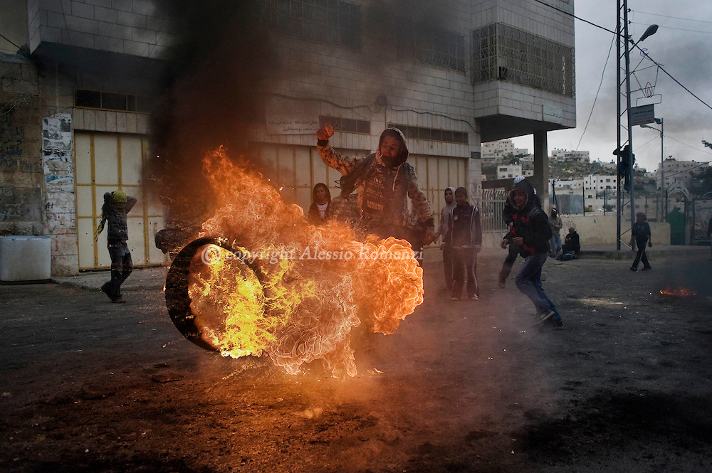 HEBRON : A Palestinian demonstrator kicks a burning tyre during clashes with Israeli forces in the West Bank town of Hebron on February 25, 2010. Around 100 Palestinians clashed with Israeli troops in Hebron over an Israeli plan to renovate two deeply contested holy sites in the occupied territory..© ALESSIO ROMENZI