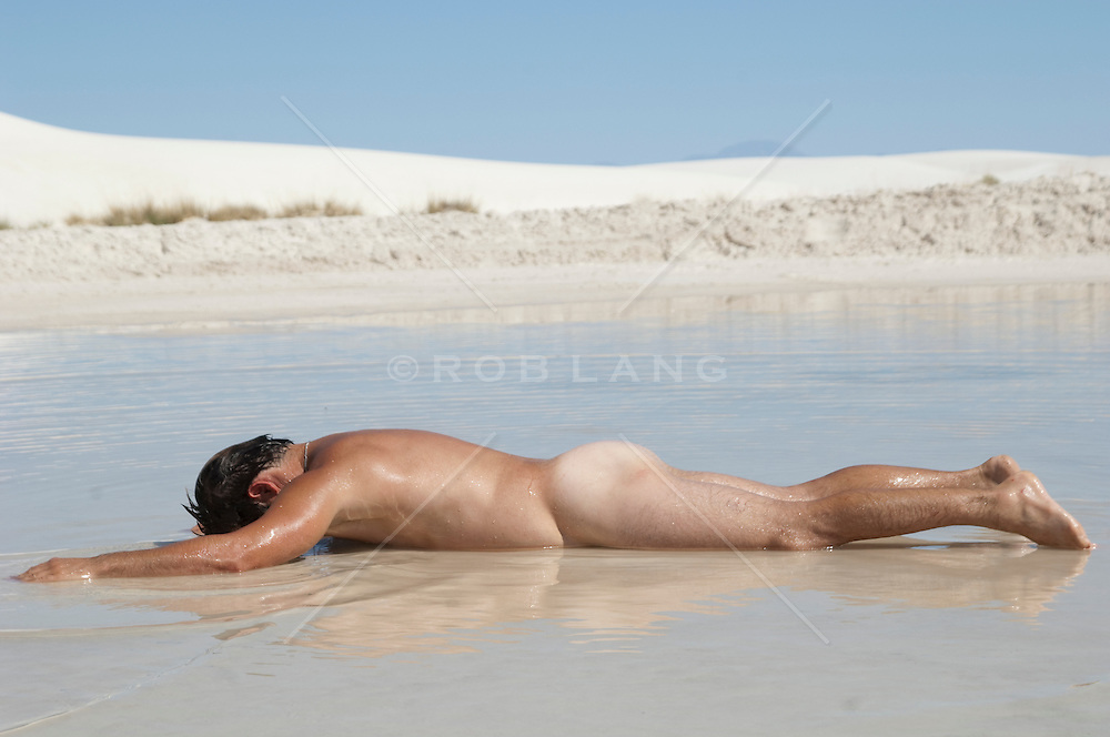 naked man face down in shallow water in White Sands National Park, NM