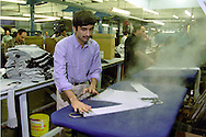 Knitwear factory worker steam pressing a garment in Northern England....