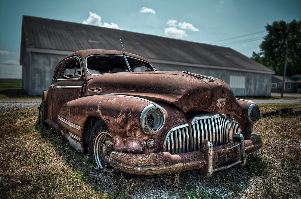 Rusty 1942 Buick automobile with front damage and broken headlights, no glass