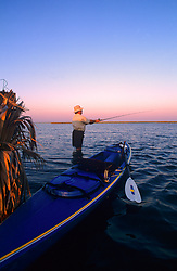 Stock photo of a man wade fishing beside his kayak near the shore at sunset