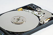 Inside an open data storage computer portable hard disk drive. View of spindle and arm.