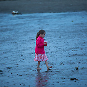 Little girl walking on the beach as it gets dark.<br />