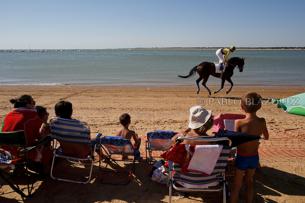 12/08/2016. A jockey rides his horse along the beach during the beach horse races on August 12, 2016 in Sanlucar de Barrameda, Cadiz province, Spain. Sanlucar de Barrameda yearly horse races traditional origin started with informal races of horse's owners delivering fish from the port to the markets. But the first formal races date back to 1845 and they are the second oldest in Spain, after Madrid. The horse races take place near the Guadalquivir river mouth during August