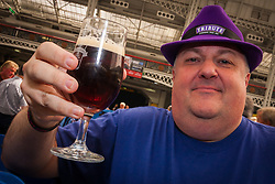 Olympia, London, August 12th 2014. A visitor to the CAMRA Great British Beer Festival raises his glass as over 900 ales, beers and ciders are exhibited at London's Olympia Exhibition Centre.