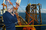 KEVIN BARTRAM/The Daily News.El Paso Corporation consultant Larry Cutburth videotapes an offshore platform as it is lifted from the Gulf of Mexico on Tuesday, June 28, 2005. The top half of the platform was lifted and placed onto the floor of the gulf near the base to form an artificial reef in about 200 feet of water 100 miles south of Galveston.