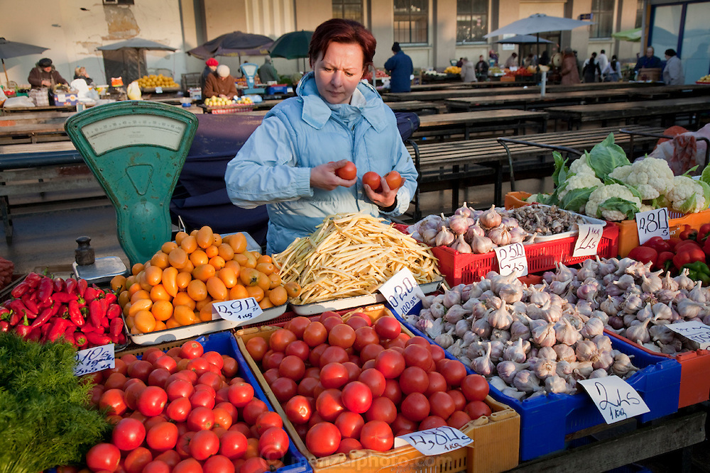 A vendor arranges vegetables on her stall at the Central Market in Riga, the capital of Latvia. Riga's Central Market, established in 1201, is one of Europe's largest and most ancient markets.