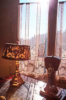 Late afternoon sun illuminates a desk lamp inside Casa Mila in Barcelona, Spain