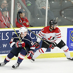 COBOURG, - Dec 15, 2015 -  Game #5 - Canada West vs the United States at the 2015 World Junior A Challenge at the Cobourg Community Centre, ON. Carson Meyer #18 of Team United States and Noah Bauld #23 of Team Canada West follows the play during the first period.(Photo: Tim Bates / OJHL Images)