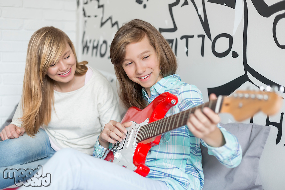 Girl listening to sister playing guitar at home