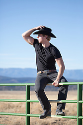 cowboy sitting on a ranch fence