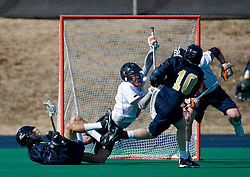 Virginia Goalie Bud Petit (8) dives to make a save after a shot by Navy attackman Gregory Clement (10).  The Virginia Cavaliers scrimmaged the Navy Midshipmen in lacrosse at the University Hall Turf Field  in Charlottesville, VA on February 2, 2008.
